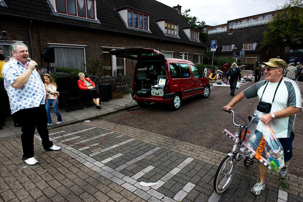 Een volkszanger zingt in de Boomgaardlaan in de Utrechtse volkswijk Ondiep tijdens het buurtfeest 'Vredig Utrecht'. De auto van de zanger fungeert als geluidsstudio<br /> <br /> A singer during a streetparty in Utrecht