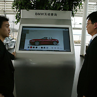 BEIJING, APRIL-22, 2010:   a sales assistant (R) answers  a customer's (L) questions   at the BMW dealership .