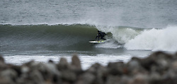 © Licensed to London News Pictures. 18/01/2014<br /> <br /> Teesside, England<br /> <br /> A surfer on the North east coast of England tucks into a barrel as he surfs a wave at a local break.<br /> <br /> Photo credit : Ian Forsyth/LNP