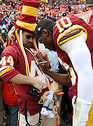 Washington Redskins quarterback Robert Griffin III (10) signs a fan autograph before the NFL week 17 regular season football game against the Dallas Cowboys on Sunday, Dec. 28, 2014 in Landover, Md. The Cowboys won the game 44-17. ©Paul Anthony Spinelli
