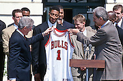 President Bill Clinton shows off his Chicago Bulls jacket gifted him by Chicago Bulls Head Coach Phil Jackson gifts President Bill Clinton a team jersey as star Scottie Pippen looks on during an event on the South Lawn of the White House April 3, 1997. The event honored the NBA Champion Chicago Bulls.