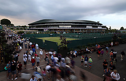 Spectators make their way around the grounds as rain falls on day three of the Wimbledon Championships at the All England Lawn Tennis and Croquet Club, Wimbledon.