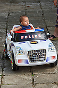 Laos. Luang Prabang.<br /> Boy with toy police car.