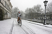Een man fietst door de sneeuw in Utrecht. Na een warme winter is het in februari eindelijk een dag winter.