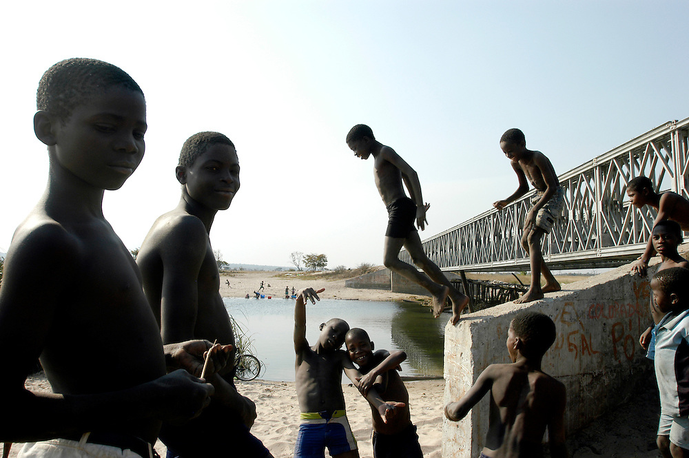 Boys playing by the river under a reconstructed bridge in the eastern province of Moxico. Infrasturcture in Angola was largely destroyed during the country's long civil war. The road and bridges between the provincial captial Luena and Lumbalagimbo, on the Zambian border, were cleared of landmines by Mines Advisory Group (MAG), allowing a major reconstruction project to take place..Mukonda, Angola. 24/07/2009..Photo © J.B. Russell