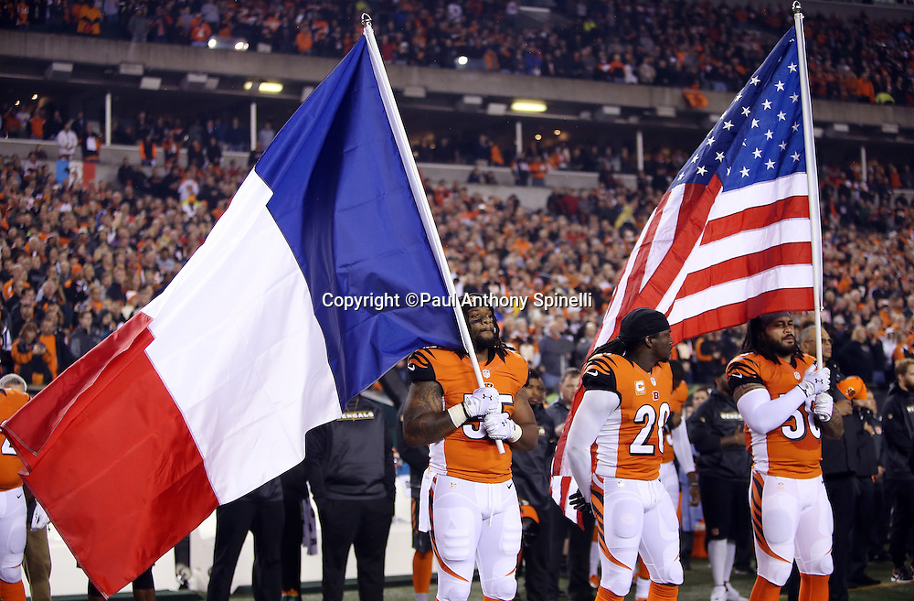 Cincinnati Bengals free safety Reggie Nelson (20) looks on as Cincinnati Bengals outside linebacker Vontaze Burfict (55) holds a French flag and Cincinnati Bengals middle linebacker Rey Maualuga (58) holds an American flag during a moment of silence in tribute to those who lost their lives and were injured in the French terrorist attack in Paris before the 2015 week 10 regular season NFL football game against the Houston Texans on Monday, Nov. 16, 2015 in Cincinnati. The Texans won the game 10-6. (©Paul Anthony Spinelli)