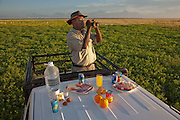 Uahoo Uahoo, a warden at Etosha National Park in northern Namibia, stands in the back of his truck with his typical day's worth of food and observes a herd of springbok. (From the book What I Eat: Around the World in 80 Diets.) MODEL RELEASED.