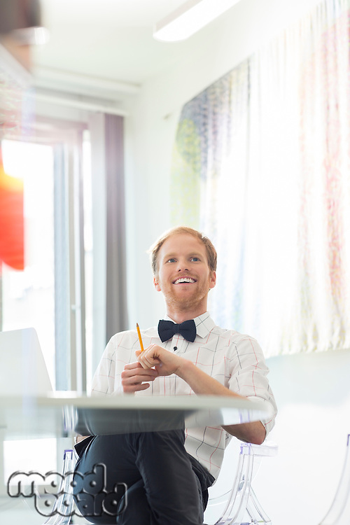 Happy businessman looking away in creative office