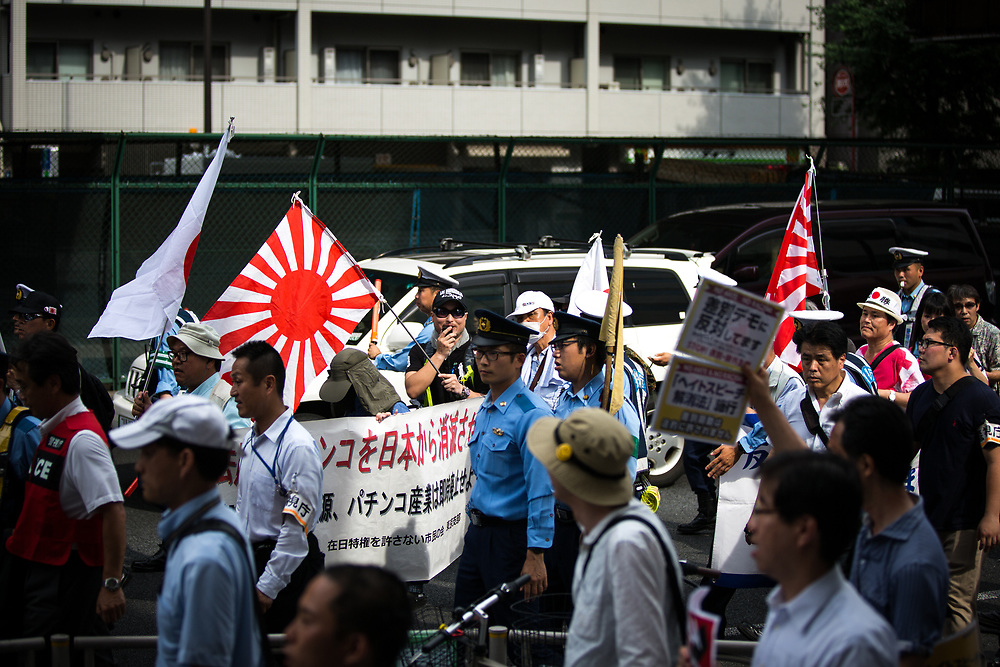 "TOKYO, JAPAN - JULY 16: Japanese nationalists holding Japanese maritime flags, escorted by police, took to the streets in a ""hate demonstration"" in Akihabara, Tokyo, Japan on July 16, 2017. The nationalists faced off with anti-racist groups who mounted counter protests demanding an end to hate speech and racism in Japan. (Photo by Richard Atrero de Guzman/NUR Photo)"