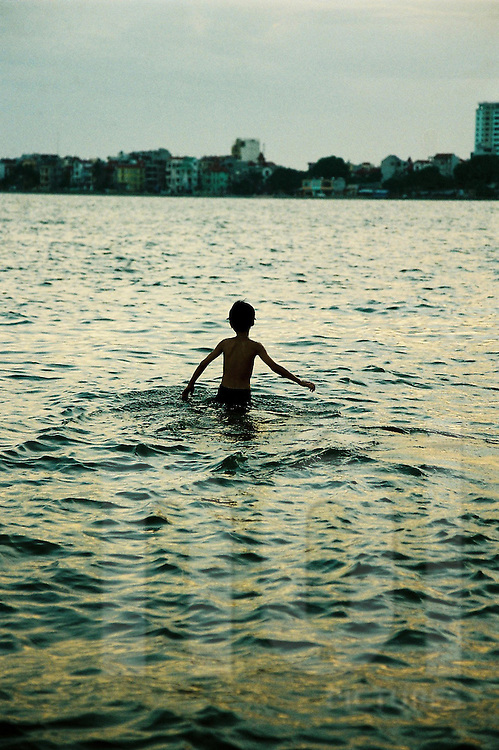 Kid going for a swim in Tay Ho (west lake) by early evening. Hanoi.