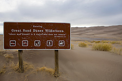 """Sign at the entrance to the dune field which reads """"Entering Great Sand Dunes Wilderness - 'where man himself is a visitor who does not remain' 1964 Wilderness Act.""""  Great Sand Dunes National Park and Preserve contains the tallest sand dunes in North America. The Dunefield, topping off with Star Dune at 750 feet, is created by sand trapped by the nearby Sangre de Christo Mountains (larger rougher grains and pebbles) and the San Juan Mountains (65 miles to the west).  Waterways such as Medano Creek help carry the sediment down to the San Luis valley where the dunes are found. Great Sand Dunes National Park and Preserve, Mosca, Colorado."""