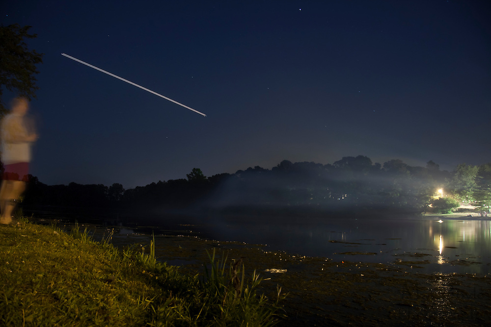 A spectator watches the smoke from the fireworks clear up over Alcyon Lake.