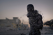 Port-au-Prince, HAITI, 20/03/2011: One year after the massive earthquake hit Haiti's capital, people try to recover their quotidian life, in the middle of a destructed city. In the early morning a man has his bath in the middle of the street with water from sewerage. (photo: Caio Guatelli)