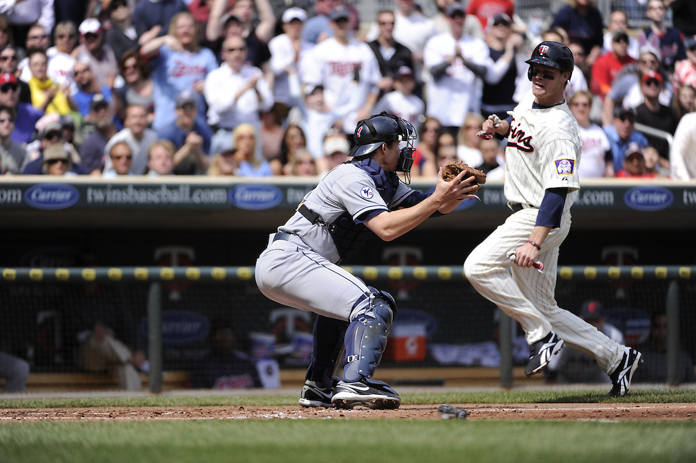 MINNEAPOLIS - APRIL 24:  Lou Marson #6 of the Cleveland Indians tags out Justin Morneau #33 of the Minnesota Twins at home plate in the third inning on April 24, 2011 at Target Field in Minneapolis, Minnesota.  The Twins defeated the Indians 4-3.  (Photo by Ron Vesely)  Subject:  Lou Marson;Justin Morneau