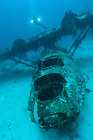 Cameraman filming the wreck of a PBY Catalina seaplane or flying boat underwater, Biak, West Papua, Indonesia.