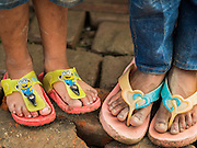 "05 AUGUST 2015 - KATHMANDU, NEPAL:  Children, one with ""Minions"" flip flops, stand on the brick floor in their tent in a large Internal Displaced Person (IDP) Camp in the center of Kathmandu. The camp is next to one the most expensive international hotels in Kathmandu. More than 7,100 people displaced by the Nepal earthquake in April live in 1,800 tents spread across the space of three football fields. There is no electricity in the camp. International NGOs provide water and dug latrines on the edge of the camp but the domestic waste water, from people doing laundry or dishes, runs between the tents. Most of the ground in the camp is muddy from the running water and frequent rain. Most of the camp's residents come from the mountains in northern Nepal, 8 - 12 hours from Kathmandu. The residents don't get rations or food assistance so every day many of them walk the streets of Kathmandu looking for day work.     PHOTO BY JACK KURTZ"