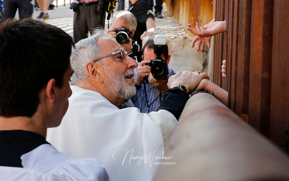 Bishop Gerald F. Kicanas of Tucson, Ariz., blesses people on the Mexican side as he distributes Communion through the border fence in Nogales, Ariz., April 1. A group of U.S. bishops, led by Cardinal Sean P. O'Malley of Boston, celebrated Mass at the border calling attention to the plight of migrants and appealing for changes in U.S. immigration policy. (CNS photo/Nancy Wiechec) (April 1, 2014) See BORDER-MASS April 1, 2014.