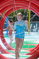 young girl runs through the water at a water park having fun during the summertime smiling at the camera.Model Released