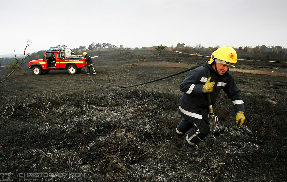 Dorset Fire Fighter Matt Norman and Crew Manager Nick Corben on Canford Heath in Poole damping down hotspots left after a wildfire destroyed a large area of the heath. Around 100 people evacuated from their homes have now been allowed to return. Twenty-five fire engines and 12 Land Rovers were involved in the battle last night to get the blaze under control.