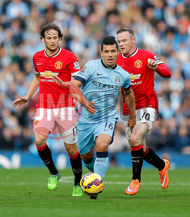 Sergio Aguero of Manchester City breaks from Daley Blind and Wayne Rooney of Manchester United - Photo mandatory by-line: Rogan Thomson/JMP - 07966 386802 - 02/11/2014 - SPORT - FOOTBALL - Manchester, England - Etihad Stadium - Manchester City v Manchester United - Barclays Premier League.