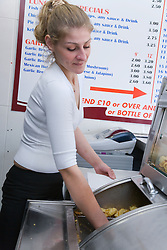 Bulgarian woman owner of fish and chip shop serving chips out of a deep fat fryer,