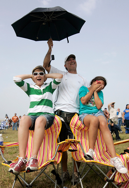 Michael Zamora/Caller-Times.Molly Sawhook (cq)(left), Claudia Leal, both 10, and Leal's father, Amando(cq), react as the sound of the jets roars over across crowd Saturday, April 18, 2009 during the South Texas Shoot Out airshow at Naval Air Station Corpus Christi.