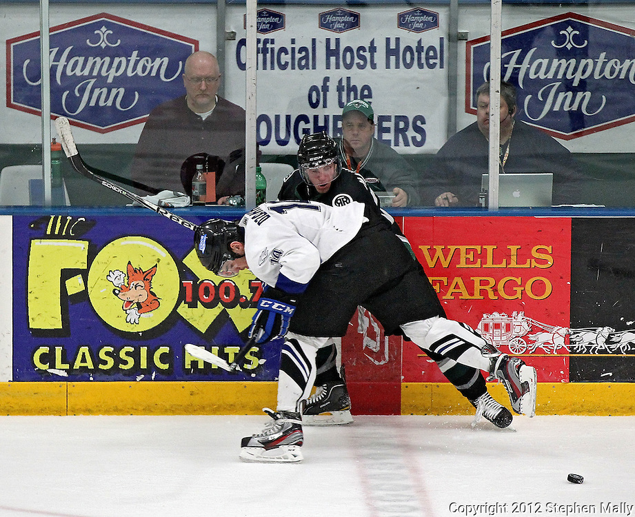 Gazette reporter Jeff Johnson (left) looks on as Roughriders Gerry Mayhew (20) tries to get around Force's Stanislav Dzhakov (14) during the game at the Cedar Rapids Ice Arena, 1100 Rockford Road SW in Cedar Rapids on Saturday evening, February 18, 2012. (Stephen Mally/Freelance)
