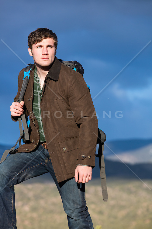 good looking man hiking on a mountain range at sunset