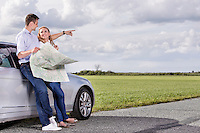 Full length of couple with map discussing direction while leaning on car at countryside