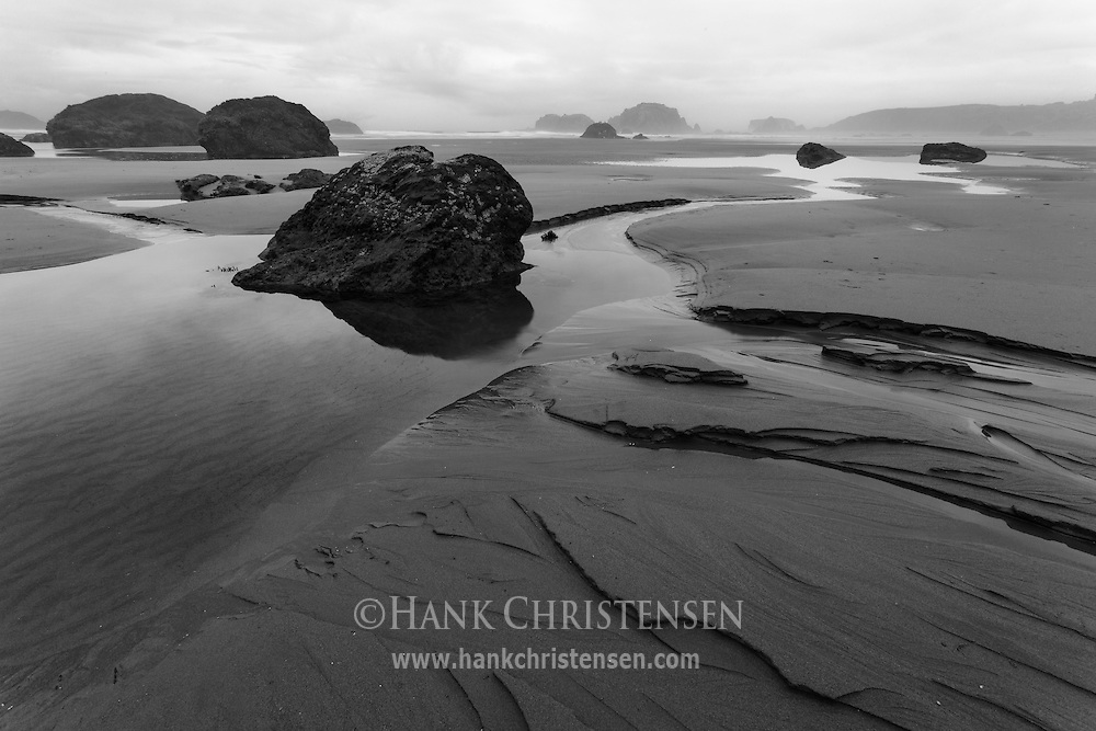 A low tide exposes large stones and carved sand along Bandon Beach, Oregon