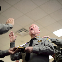 010914      Cayla Nimmo<br /> <br /> Sheriff's deputy Bob Brittain and his fellow officers participate in a group swearing in ceremony lead by Sheriff Tony Mace and Magistrate Judge Johnny Valdez on Friday morning in Grants.