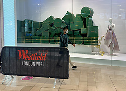 © Licensed to London News Pictures. 03/07/2020. London, UK. A man wearing a face mask walks past a shop window display at Westfield Shopping Centre in Shepherd's Bush, West London at the opening of Harrods Outlet store. Photo credit: Ben Cawthra/LNP