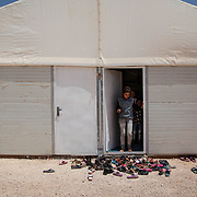 At the entrance to a Mercy Corps child friendly space children remove their shoes before entering the caravan, as is custom to remove ones shoes before entering a room in Arab culture. Azraq camp for Syrian refugees, Jordan, May 2014.