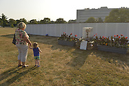 """East Meadow, New York, U.S. 11th September 2013. A woman and toddler girl visit the Global War on Terror """"Wall of Remembrance"""" a traveling memorial on display in New York for the first time, at Eisenhower Park on the 12th Anniversary of the terrorist attacks of 9/11. The unique 94 feet long by 6 feet high wall has, on one side, almost 11,000 names of those lost on September 11, 2001, along with heroes and veterans who lost their lives defending freedom of Americans over past 30 years. On the wall's other side is a timeline, with photos, covering 1983 to present day."""