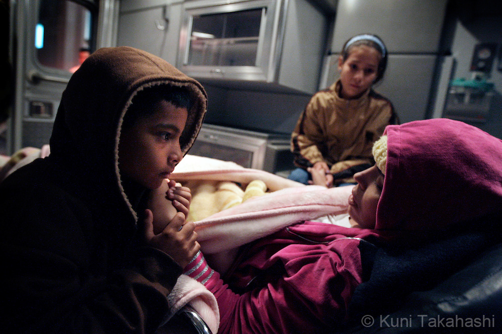 Mariana de la Torre, 29, holds the hands of her children Rodrigo, 8, and Andrea, 11, in an ambulance after arriving at Morelia airport in Mexico on Feb 23, 2009.<br />  (Photo by Kuni Takahashi)