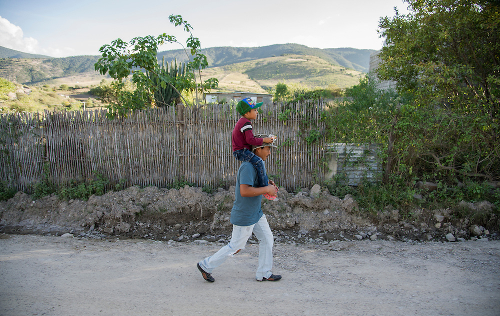After a trip to Santa Ana's center for sweets, Santiago Garcia gives his son, Leandro, a shoulder-ride home on the same road he grew up. His love of the land has influenced his decision to build a home and start a family on the same plot of land as his parent's home. Nick Wagner / Alexia Foundation