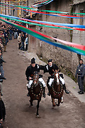 Riders in pairs gallop down a back street in the hilltop village of Santu Lussurgiu during Su Carrela 'e Nanti festival at the end of carnival and the beginning of Lent, Sardinia, Italy
