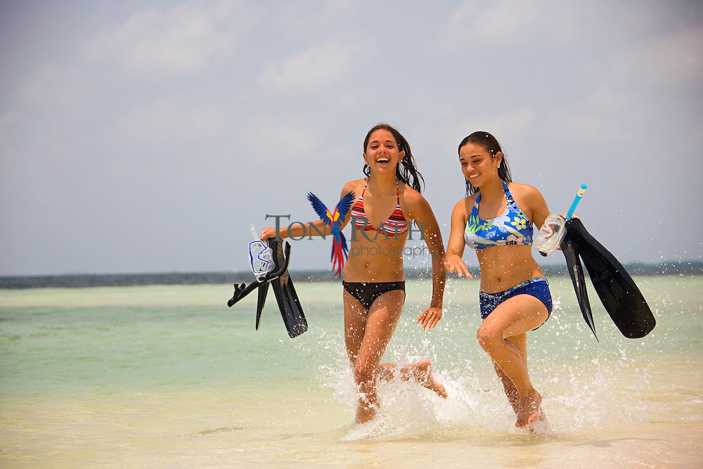 Two young women playing on south beach at South Water Caye, Belize
