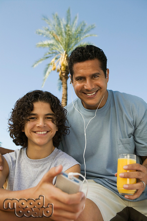 Father and Son Listening to MP3 Player and Drinking Juice