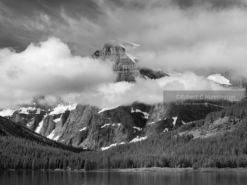 Cloud and mist add drama to this monochrome study of Mount Gould. in the Many Glacier region of Glacier National Park, Montana, USA