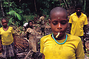 Asmattan child with Ulat-Kayu (wood grub in Indonesia) down river from Sawa Village, Irian Jaya, Indonesia. (Man Eating Bugs page 75 Top) .