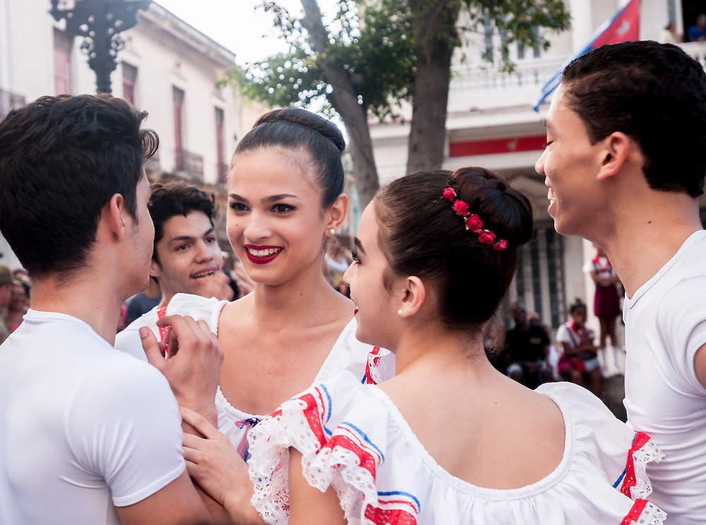 Youth ballet performers on a street in downtown Havana, Cuba share a laugh after a big fall during a performance.