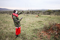 A local guide tracking the elusive lions during an evening drive on Enasoit, Kenya.