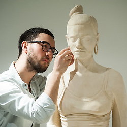 London, UK - 29 January 2014: artist Simon Fujiwara works on his terracotta-dyed life sized plaster casts. His work Rebekkah, comprising 100 terracotta-dyed life sized plaster casts of a 16-year-old girl who took part in the 2011 London riots, goes on display at the Contemporary Art Society until 29 March.