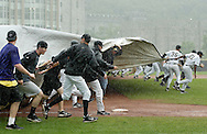 Baseball players from Army and Holy Cross pull a tarp across the field as heavy rain falls during the Patriot League championship game at West Point on Monday, May 21, 2012. Rain delays the start of the game and then more rain suspended the game with the score tied 4-4 in the top of the seventh inning. The game is scheduled to resume at 2 p.m. Tuesday. The teams split the first two game of the best-of-three series.