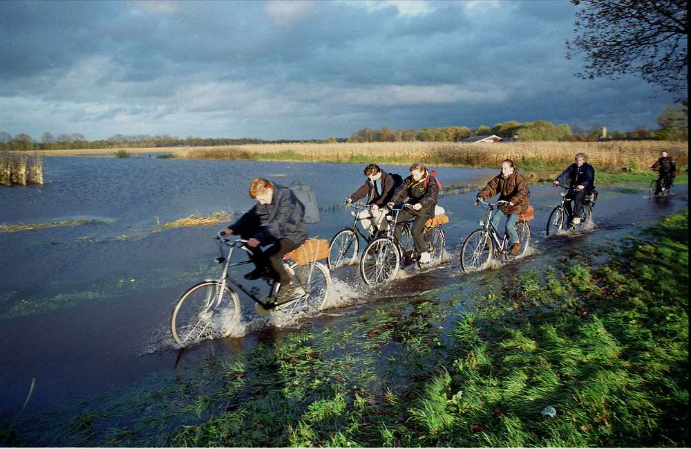 Nederland. Boekel, 03-11-1999<br /> Schoolkinderen op weg naar huis rijden over een ondergelopen fietspad. Door hevige regenval is het riviertje de Dommel buiten zijn oevers getreden en heeft op een paar plekken de wegen overstoomd, maar dat maakt het naar huis fietsen niet minder leuk. De overstroming was lastig, maar niet rampzalig. Wateroverlast. Scholieren op de fiets met schooltas.<br /> Foto: Michiel Wijnbergh/Hollandse Hoogte