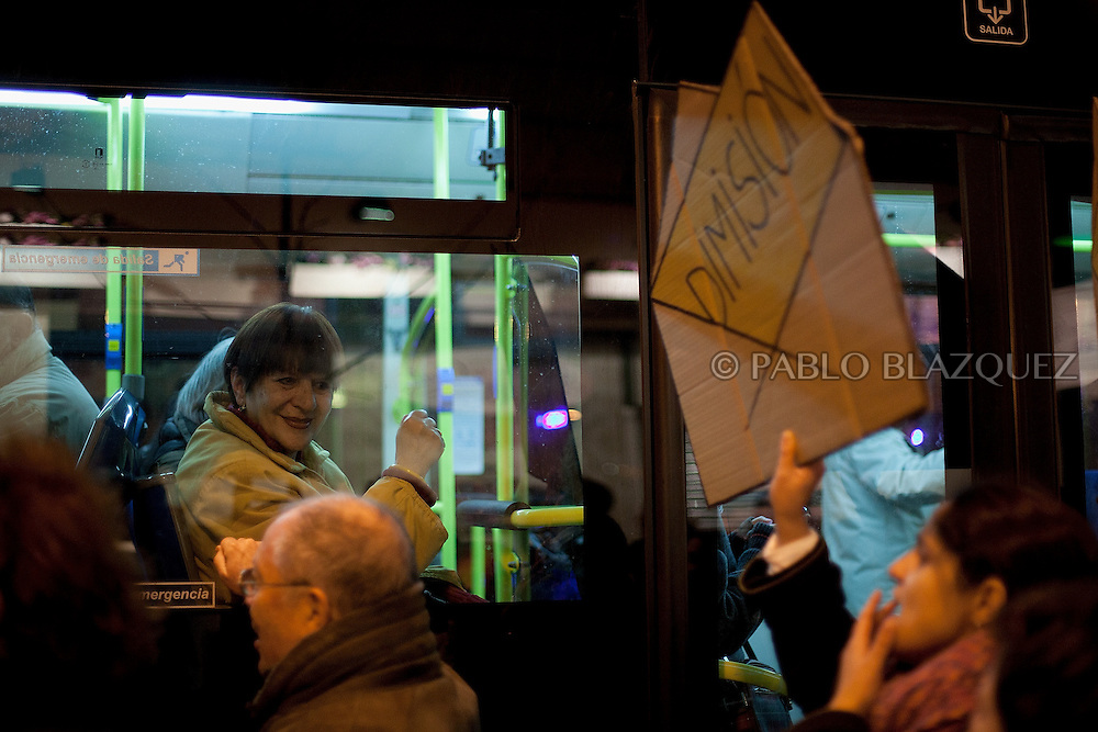 Protesters walk in the streets while a woman inside a bus support them during a demonstration against political corruption and claiming Mariano Rajoy to resign in Madrid on February 1, 2013. The Spanish Newspaper 'El Pais' published secret papers of income implicating Spanish Prime Minister and other members of the PP (Popular Party). Rajoy's government has denied these secret payments.