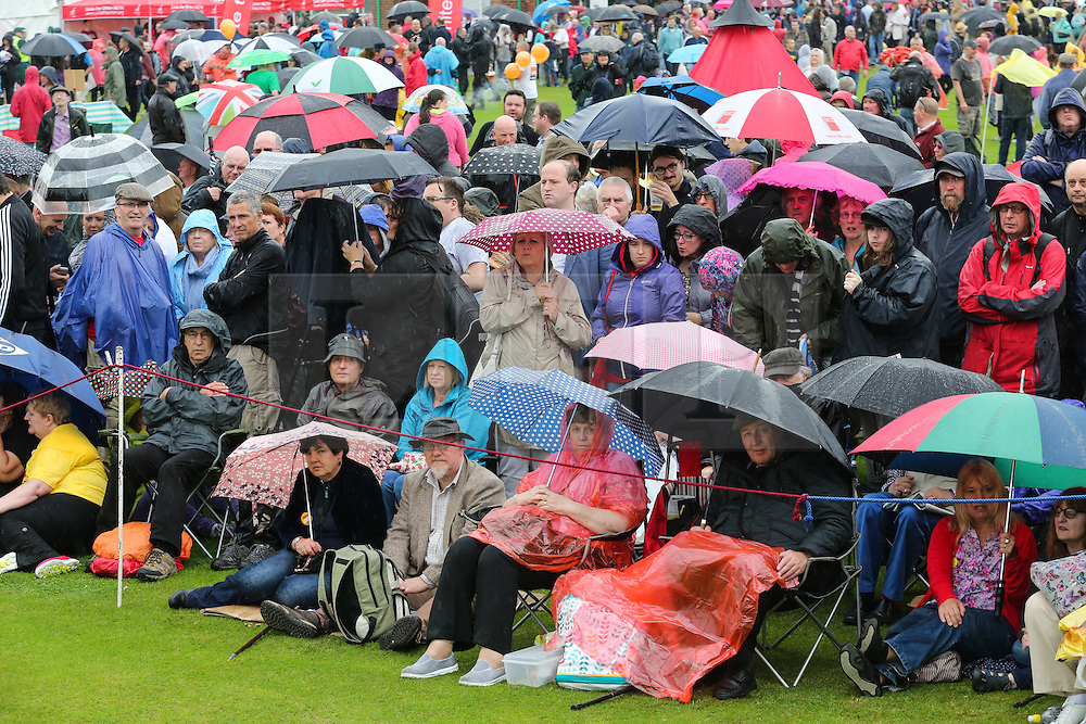 © Licensed to London News Pictures. 09/07/2016. Durham, UK. Visiters cover themselves with umbrellas and jackets as the rain pours down at the Durham Miners' Gala in County Durham, UK. The gala is a large gathering held annually associated with the coal mining heritage and trade unionism. Photo credit : Ian Hinchliffe/LNP