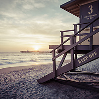 San Clemente Lifeguard Tower 3 sunset picture. In the background is San Clemente Pier with the sun setting above it. Photo is high resolution. Copyright ⓒ 2017 Paul Velgos with All Rights Reserved.