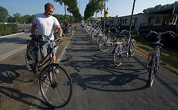 Tourists from Germany enjoy a Boat and Bike tour through Flanders. A tour member prepares his bike before leaving for the morning ride from Bruges to Damme, in the Flemish region of Belgium, on Sunday, July 11, 2010. (Photo © Jock Fistick)
